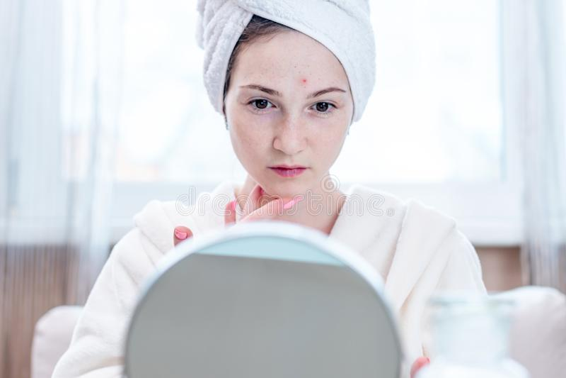 A jovem mulher infeliz bonita detecta a acne em sua cara Conceito da higiene e do cuidado para a pele foto de stock royalty free