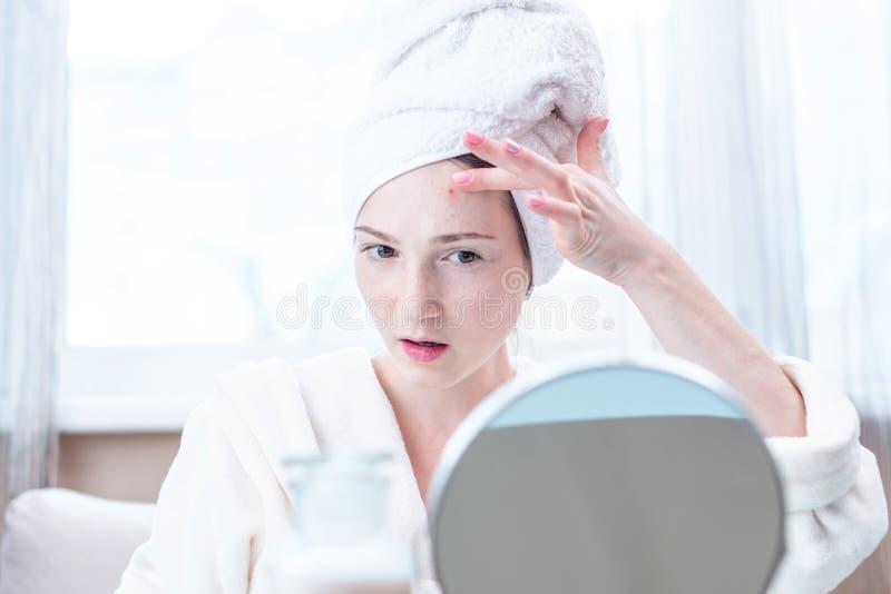 Jovem mulher infeliz bonita que olha a acne em sua cara Conceito da higiene e do cuidado para a pele foto de stock royalty free