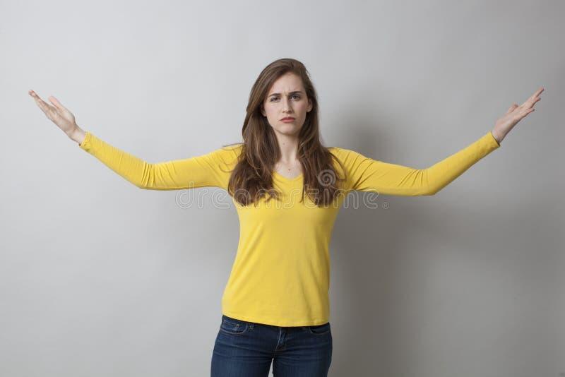 A jovem mulher infeliz com os braços largos abre foto de stock