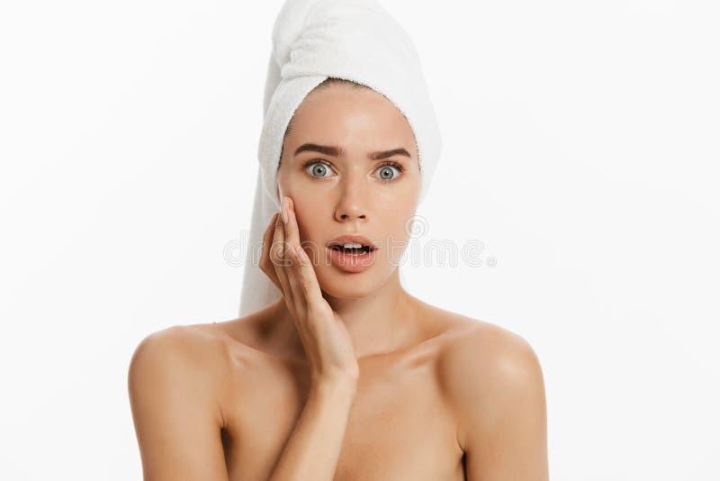 Jovem mulher infeliz que encontra uma acne em um mordente Isolado no fundo branco fotos de stock royalty free