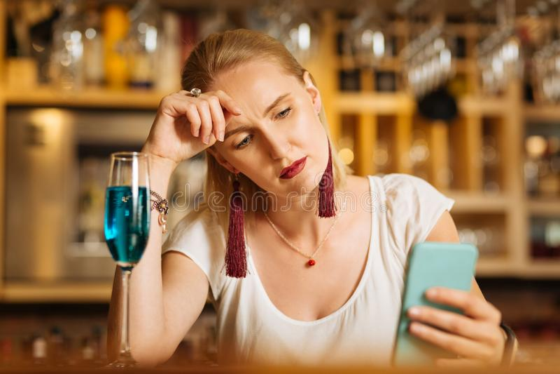 Jovem mulher infeliz que usa seu smartphone moderno fotos de stock