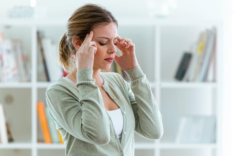Jovem mulher insalubre com a dor de cabeça que toca em sua cabeça em casa imagens de stock royalty free