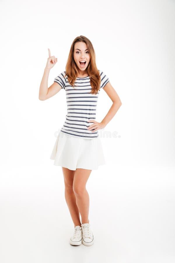 Jovem mulher inspirada feliz que aponta acima e que tem uma ideia fotografia de stock royalty free