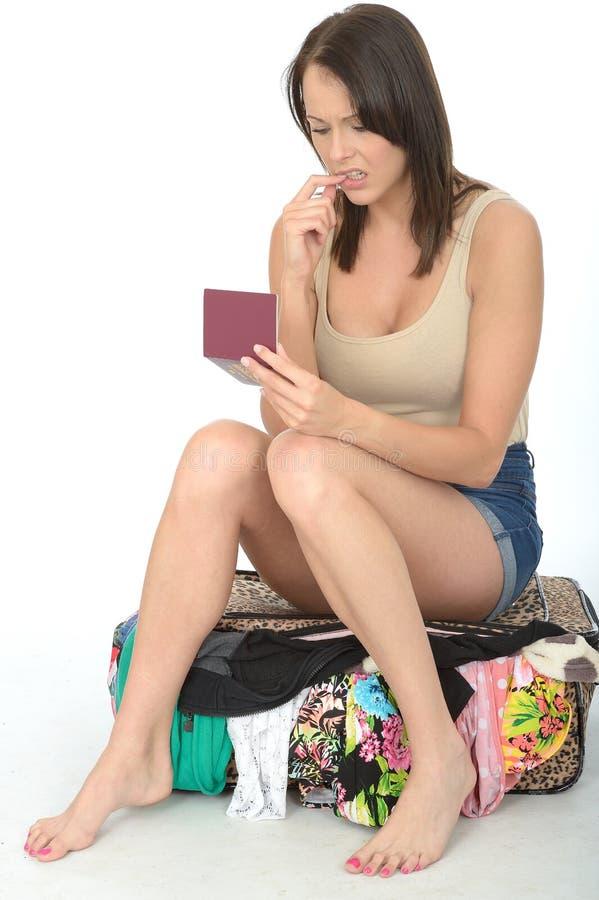 Jovem mulher interessada ansiosa que senta-se em uma mala de viagem de transbordamento que guarda um passaporte que olha preocupa imagens de stock