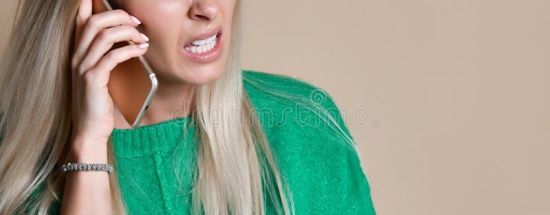 Jovem mulher irritada que discute a fala no telefone fotografia de stock