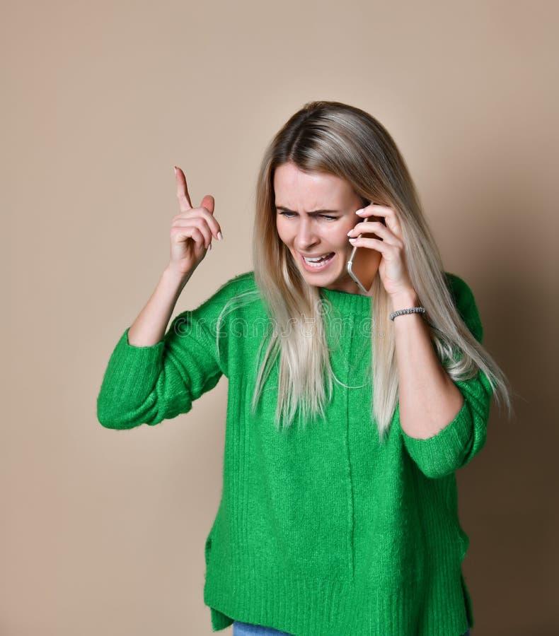 Jovem mulher irritada que discute a fala no telefone fotos de stock