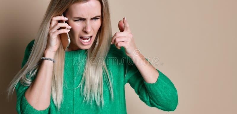 Jovem mulher irritada que discute a fala no telefone imagem de stock