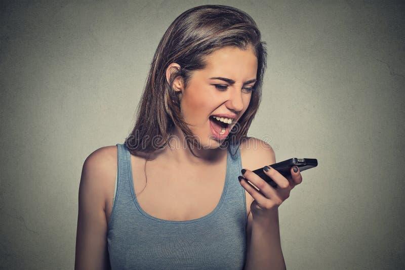 Jovem mulher irritada que grita no telefone celular foto de stock