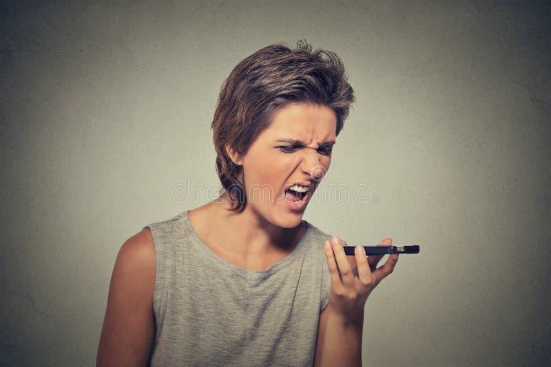 Jovem mulher irritada que grita no telefone celular fotografia de stock