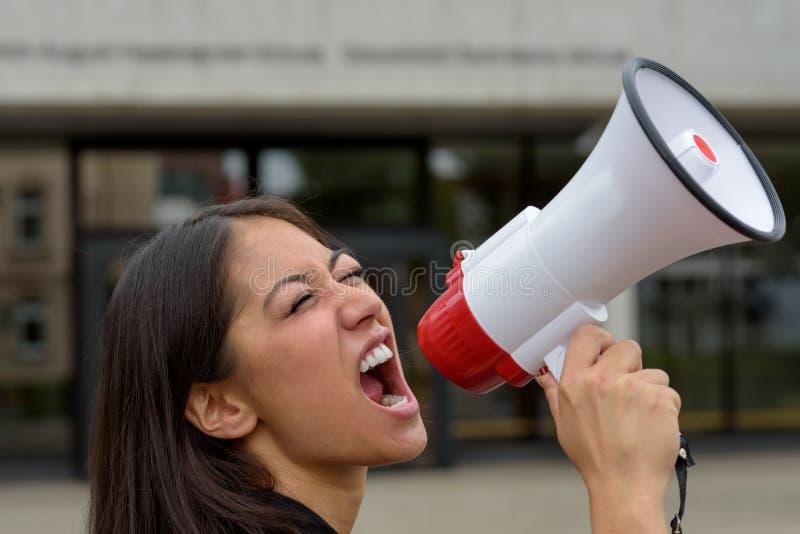 Jovem mulher irritada que grita sobre um megafone fotos de stock royalty free