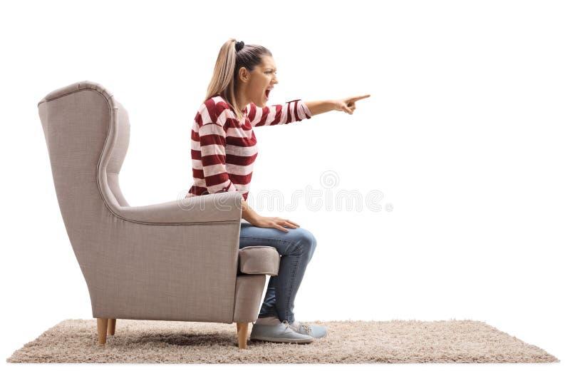 Jovem mulher irritada que senta-se em uma poltrona e em uma argumentação imagens de stock