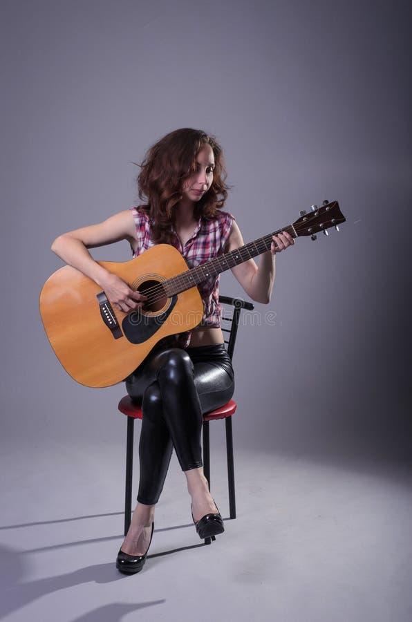 A jovem mulher joga em uma guitarra acústica, isolada em um cinza para trás foto de stock royalty free
