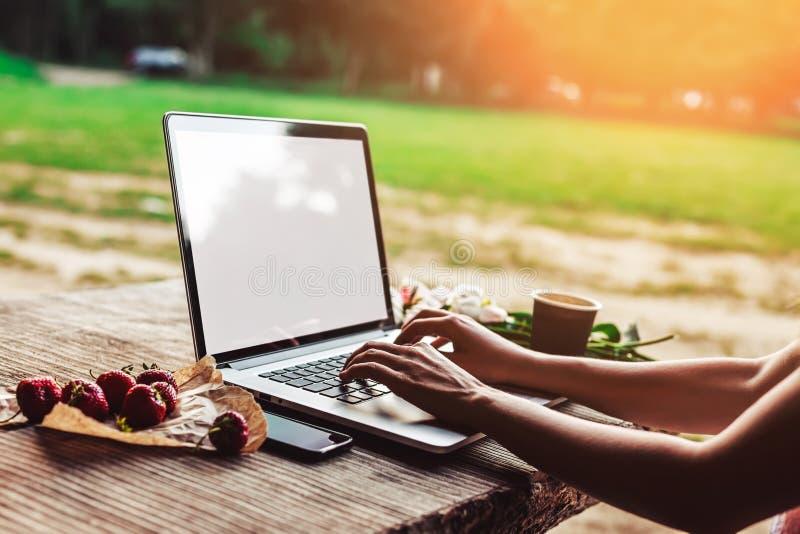 A jovem mulher laptop de utilização e de datilografia na tabela de madeira áspera com copo de café, morangos, ramalhete das peôni fotografia de stock royalty free