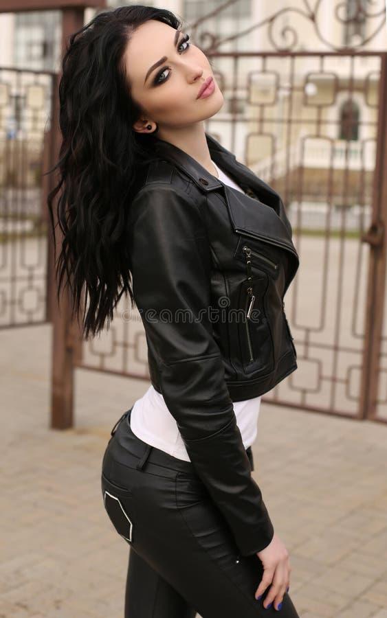 Jovem mulher lindo com cabelo escuro na roupa ocasional, j de couro imagens de stock royalty free