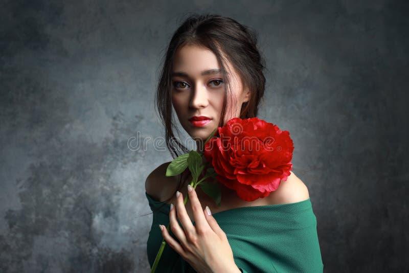 Jovem mulher lindo com a composição brilhante que levanta com flores da peônia Perfumes e cosm?ticos Conceito da forma imagens de stock
