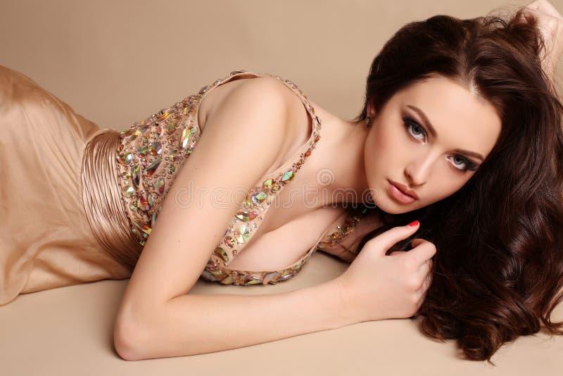 A jovem mulher lindo com composição do cabelo escuro e da noite, veste o vestido luxuoso imagem de stock