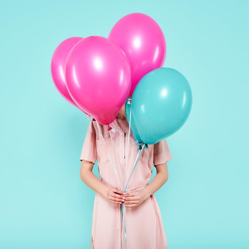 A jovem mulher lindo no equipamento do partido que guarda o grupo de balões coloridos, isolado sobre o azul pastel coloriu o fund fotografia de stock royalty free