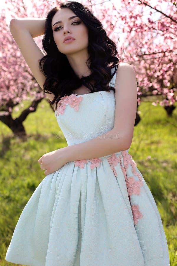 Jovem mulher lindo no vestido elegante que levanta no jardim com blos imagem de stock royalty free