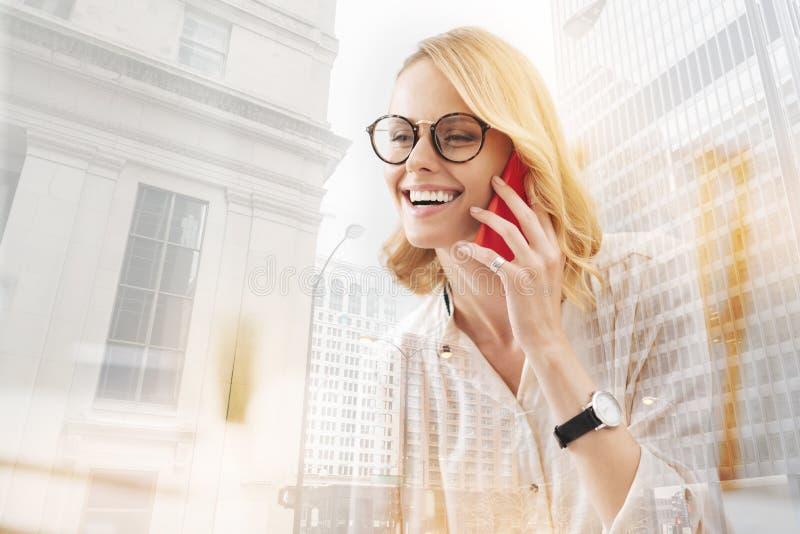 Jovem mulher lindo que comunica-se sobre o telefone celular foto de stock