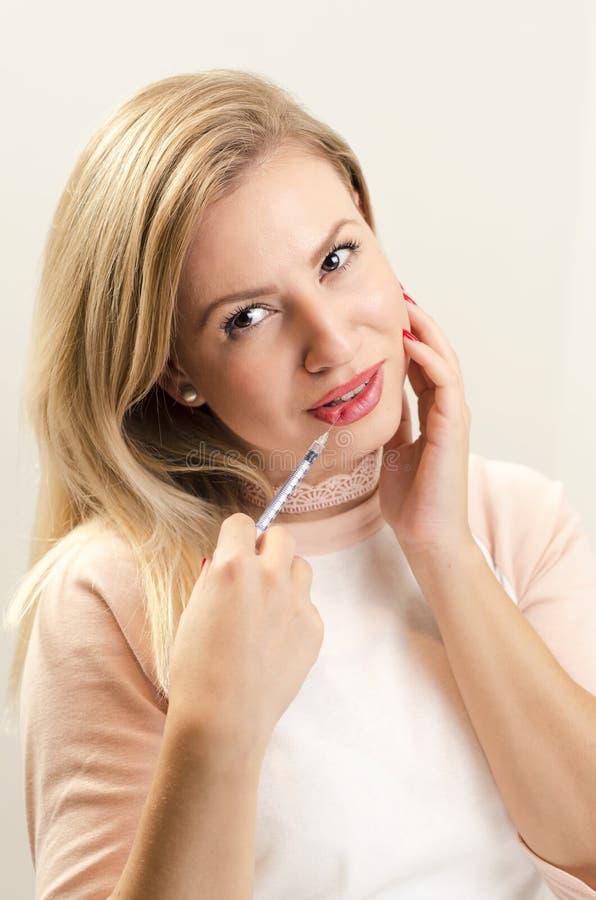 Jovem mulher lindo que guarda a seringa em seu bordo imagem de stock royalty free