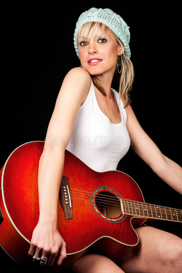 Jovem mulher lindo que guardara uma guitarra fotografia de stock royalty free