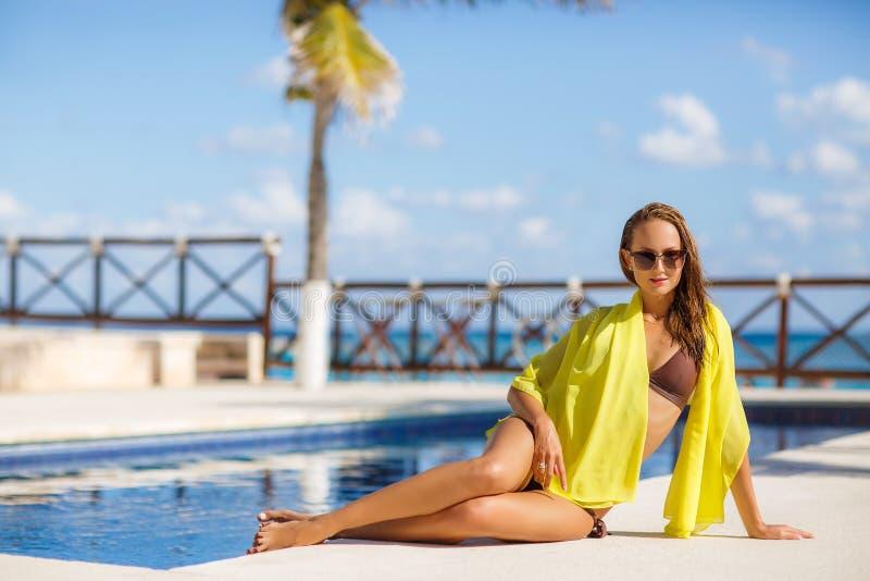 Jovem mulher lindo que levanta no biquini com o pareo amarelo perto da piscina imagens de stock royalty free
