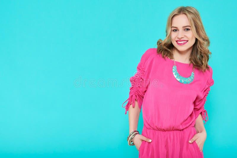 Jovem mulher loura atrativa no vestido de partido na moda e em acessórios de harmonização Menina que levanta em um fundo azul pas foto de stock
