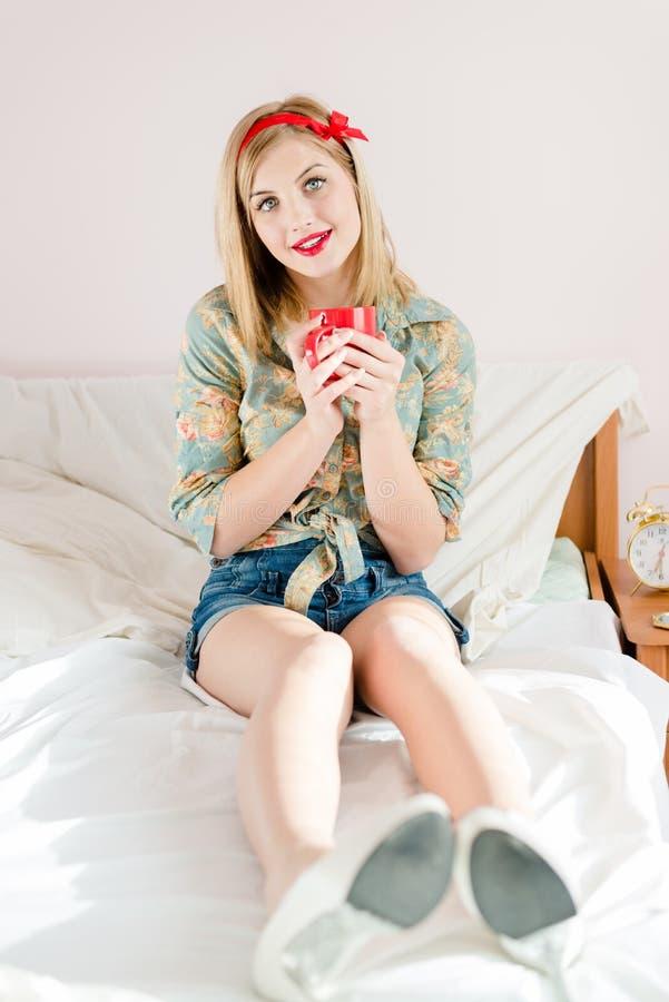 Jovem mulher loura bonita do pinup com copo vermelho fotos de stock royalty free