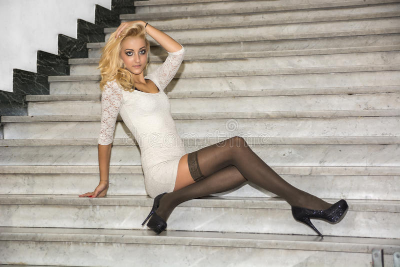 Jovem mulher loura bonita elegante que senta-se nas escadas de mármore imagem de stock royalty free