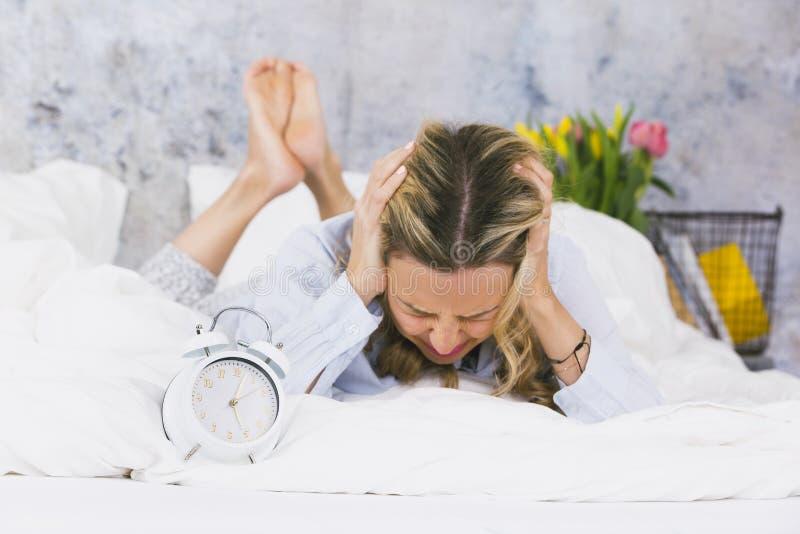 A jovem mulher loura, bonita não gosta de levantar-se na manhã e não odeia seu despertador de soada e não é frustrada fotografia de stock