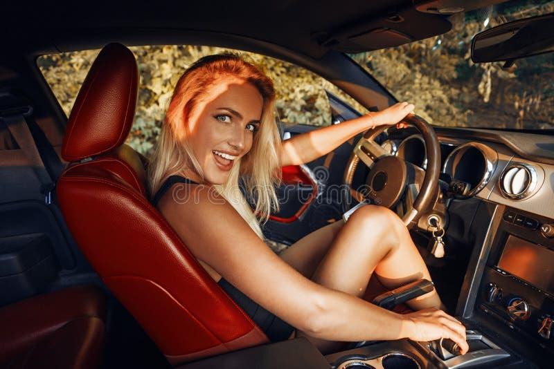 Jovem mulher loura bonita na condução preta do bodysuit fotos de stock