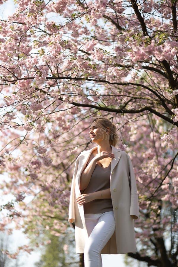 Jovem mulher loura bonita no parque de Sakura Cherry Blossom na mola que aprecia a natureza e o tempo livre durante ela que viaja imagens de stock