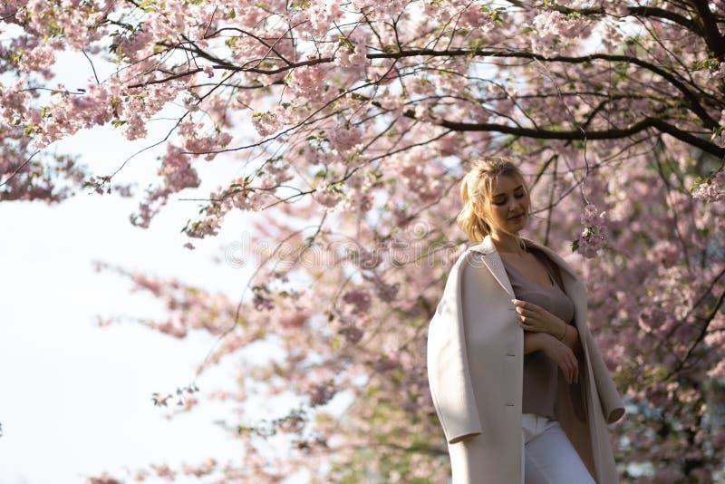 Jovem mulher loura bonita no parque de Sakura Cherry Blossom na mola que aprecia a natureza e o tempo livre durante ela que viaja imagem de stock