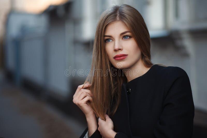 Jovem mulher loura bonita no revestimento preto agrad?vel r Foto da forma fotos de stock royalty free