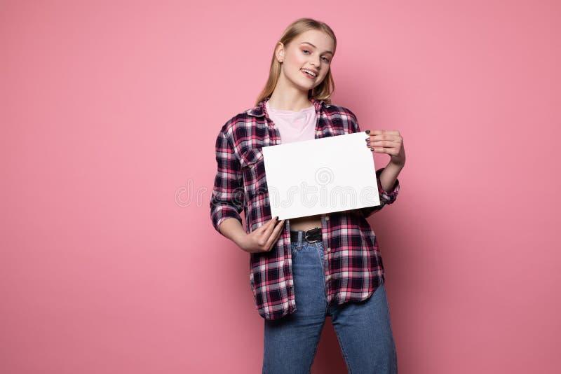 Jovem mulher loura de sorriso feliz na roupa ocasional que est? contra a parede cor-de-rosa fotos de stock royalty free