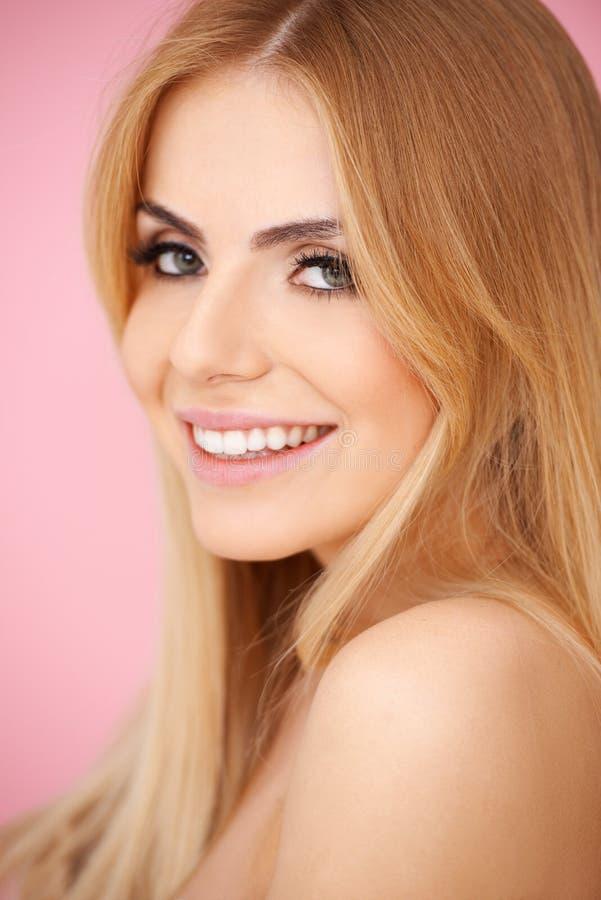 Jovem mulher loura de sorriso sobre o rosa fotografia de stock