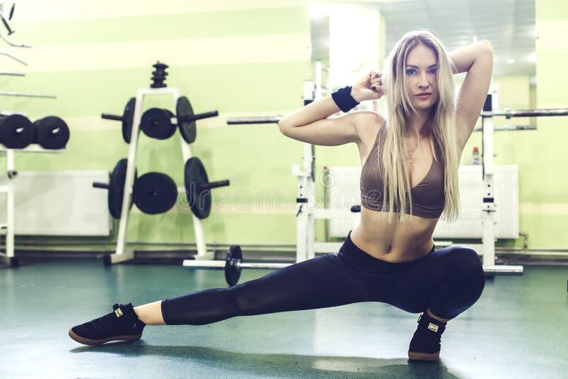 Jovem mulher loura desportiva que aquece-se antes de treinar em um GYM fotografia de stock