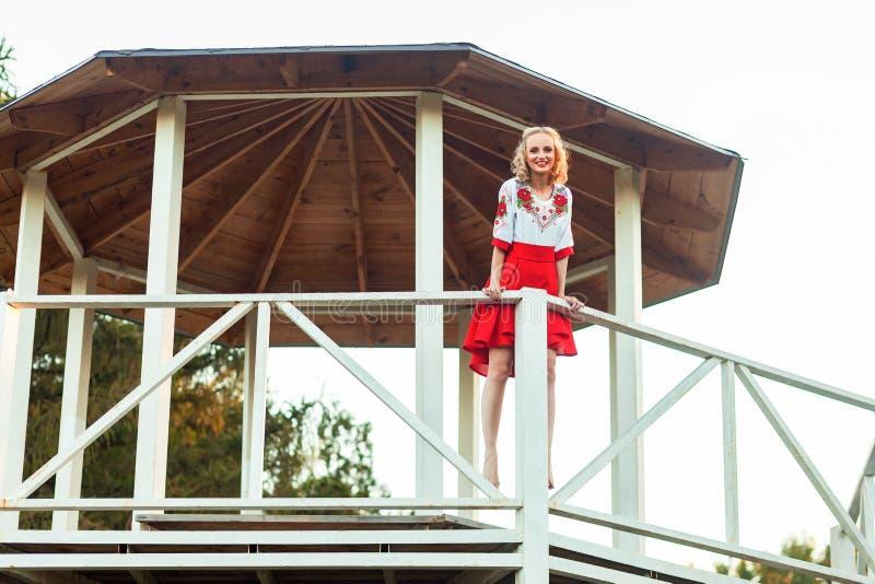 Jovem mulher loura feliz no vestido branco vermelho à moda que levanta no mandril de madeira do jardim estando e olhando a câmera imagem de stock