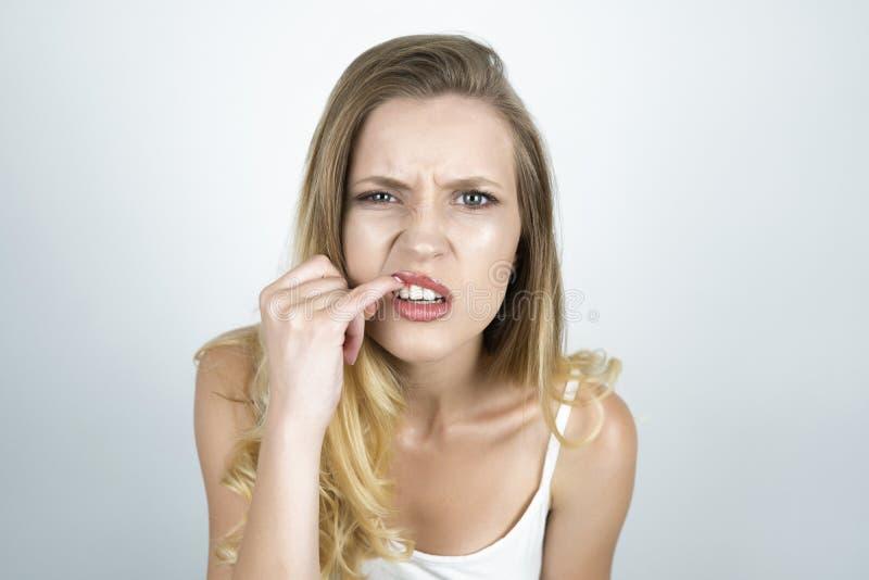 Jovem mulher loura que mostra seus dentes com fim do dedo acima do fundo branco isolado fotografia de stock royalty free