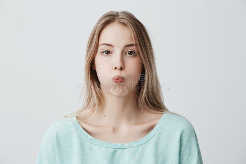 A jovem mulher loura triste tem lotas mal-humoradas da expressão seus bordos após a discussão com marido Fêmea descontentada desc fotografia de stock