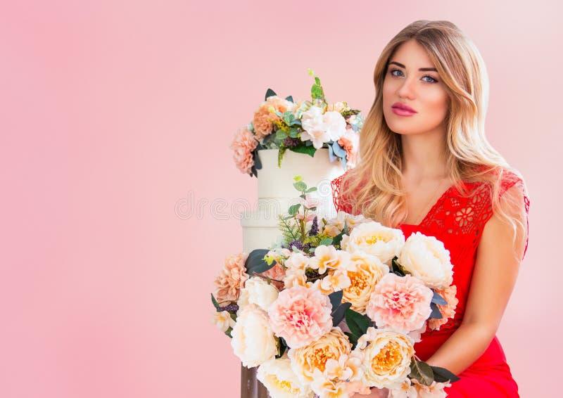 A jovem mulher macia bonita com o ramalhete da mola floresce no fundo cor-de-rosa Retrato do blonde bonito com flores fotografia de stock
