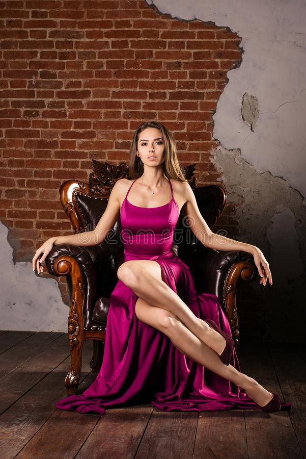 A jovem mulher magnífica no vestido luxuoso a está sentando-se em uma cadeira em um apartamento luxuoso fotos de stock royalty free