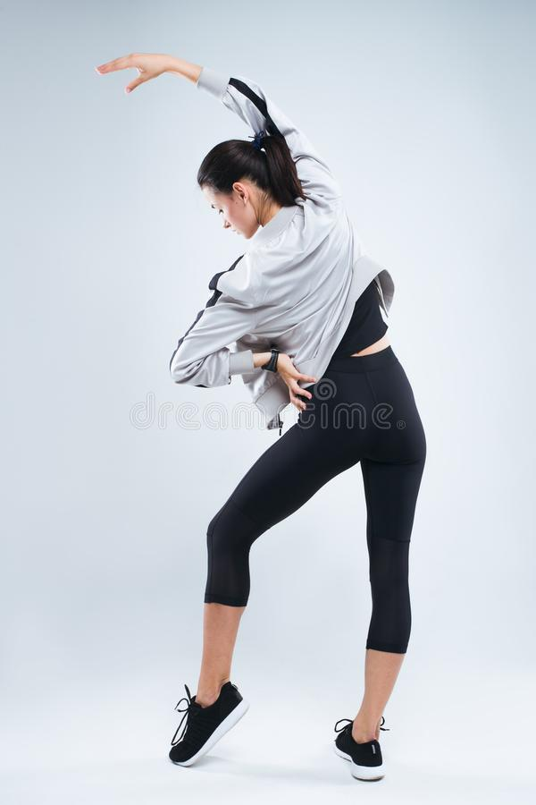 A jovem mulher magro e do esporte que levanta e que faz o esporte exercita a posição com ela de volta à câmera e os braços do est fotos de stock royalty free