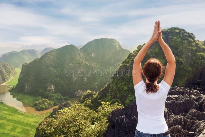 A jovem mulher mantém a calma e medita ao praticar a ioga imagens de stock royalty free