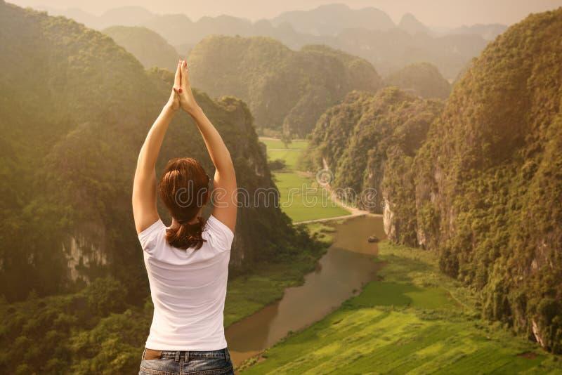 A jovem mulher mantém a calma e medita ao praticar a ioga foto de stock royalty free
