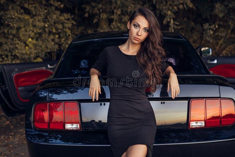 Jovem mulher marrom bonita do cabelo no levantamento preto do vestido foto de stock royalty free