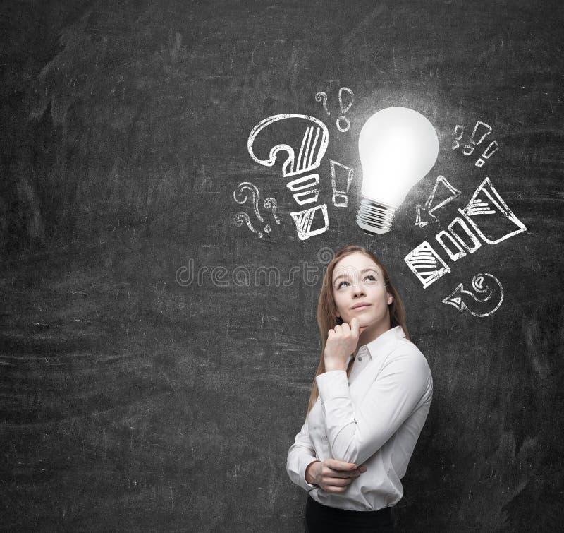 A jovem mulher medita sobre ideias novas do negócio Uma ampola como um conceito de ideias novas fotografia de stock