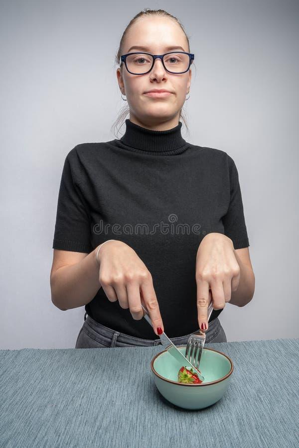 A jovem mulher minimalista corta uma única morango em uma bacia imagens de stock