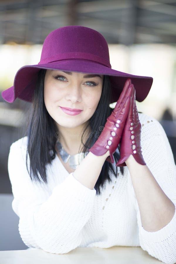 A jovem mulher misteriosa em um chapéu e em luvas de Borgonha senta-se em Ta imagem de stock royalty free