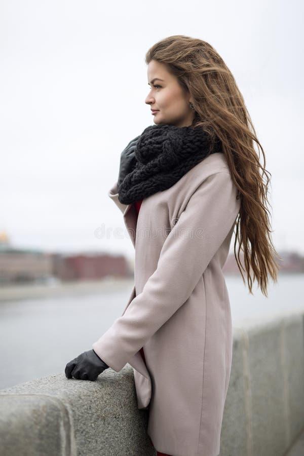 A jovem mulher misteriosa está na terraplenagem e na vista na distância Menina em um revestimento preto, em um lenço e em um vest fotos de stock
